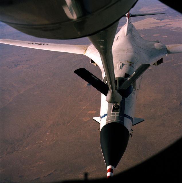 A B-1B bomber testbed aircraft refuels from an Arizona Air National Guard KC-135E Stratotanker aircraft. Edwards Air Force Base is visible below