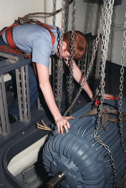 A crewman guides a new electric motor through an opening for installation in an interior space aboard the nuclear-powered aircraft carrier USS DWIGHT D. EISENHOWER (CVN 69)