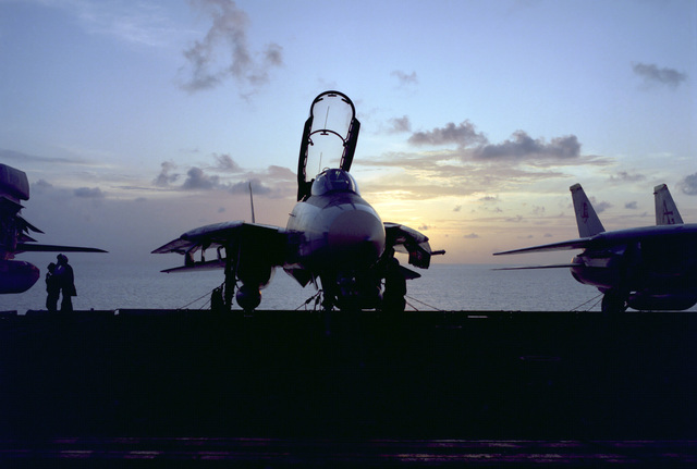A Fighter Squadron 142 (VF-142) F-14A Tomcat aircraft aboard the nuclear-powered aircraft carrier USS DWIGHT D. EISENHOWER (CVN 69) is silhouetted against a sunset