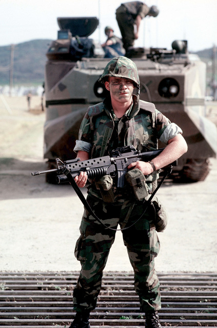 A member of the 26th Marine Amphibious Unit is armed with an M203 40 mm grenade launcher-equipped M203 40 mm grenade launcher-equipped M16A1 rifle during the joint service Exercise OCEAN VENTURE '84. He is standing in front of an LVTP7 tracked landing vehicle, personnel
