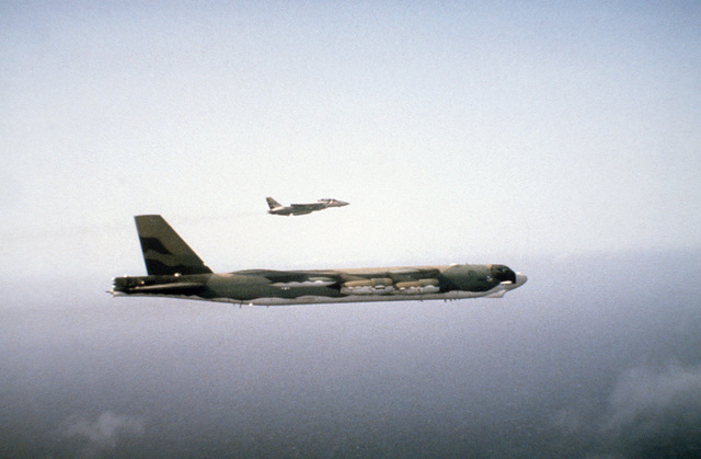 An air-to-air right side view of a US Navy F-14A Tomcat aircraft escorting a US Air Force B-52 Stratofortress aircraft