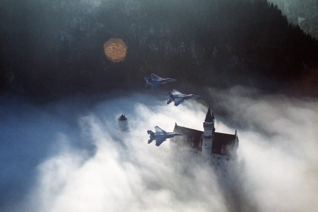 An air-to-air right side view of three F-15 Eagle aircraft from the 59th Tactical Fighter Squadron as they fly over the Castle Neuschwanstein during REFORGER '82