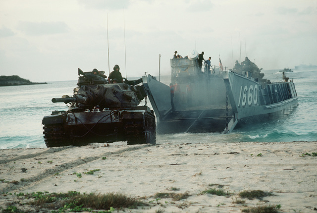 An M60 main battle tank rolls onto the beach from a utility landing craft (LCU 1660) assigned to Assault Craft Unit Two. This operation is part of the joint service Exercise OCEAN VENTURE '84