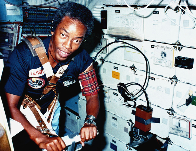 Astronaut Guion S. Bluford, mission specialist, walks on a treadmill exerciser during a medical test aboard the space shuttle orbiter Challenger (STS-8)