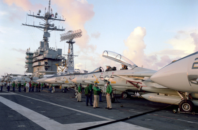 Crew members conduct a foreign object damage inspection of the flight deck prior to flight operations aboard the nuclear-powered aircraft carrier USS DWIGHT D. EISENHOWER (CVN 69). F-14A Tomcat aircraft are parked on the right
