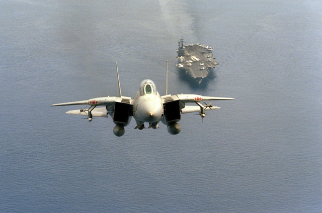 Front air-to-air view of an F-14A Tomcat aircraft from Fighter Squadron 102 (VF-102), just after taking off from the aircraft carrier USS AMERICA (CV-66). The aircraft is armed with two AIM-54 Phoenix missiles, centerline, two AIM-7 Sparrow and two AIM-9 Sidewinder missiles (outside), mounted on wing pylons