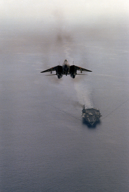 Front air-to-air view of an F-14A Tomcat aircraft from Fighter Squadron 102 (VF-102) just after taking off from the aircraft carrier USS AMERICA (CV-66). The aircraft is armed with two AIM-54 Phoenix missiles, centerline, two AIM-7 Sparrow and two AIM-9 Sidewinder missiles (outside), mounted on wing pylons