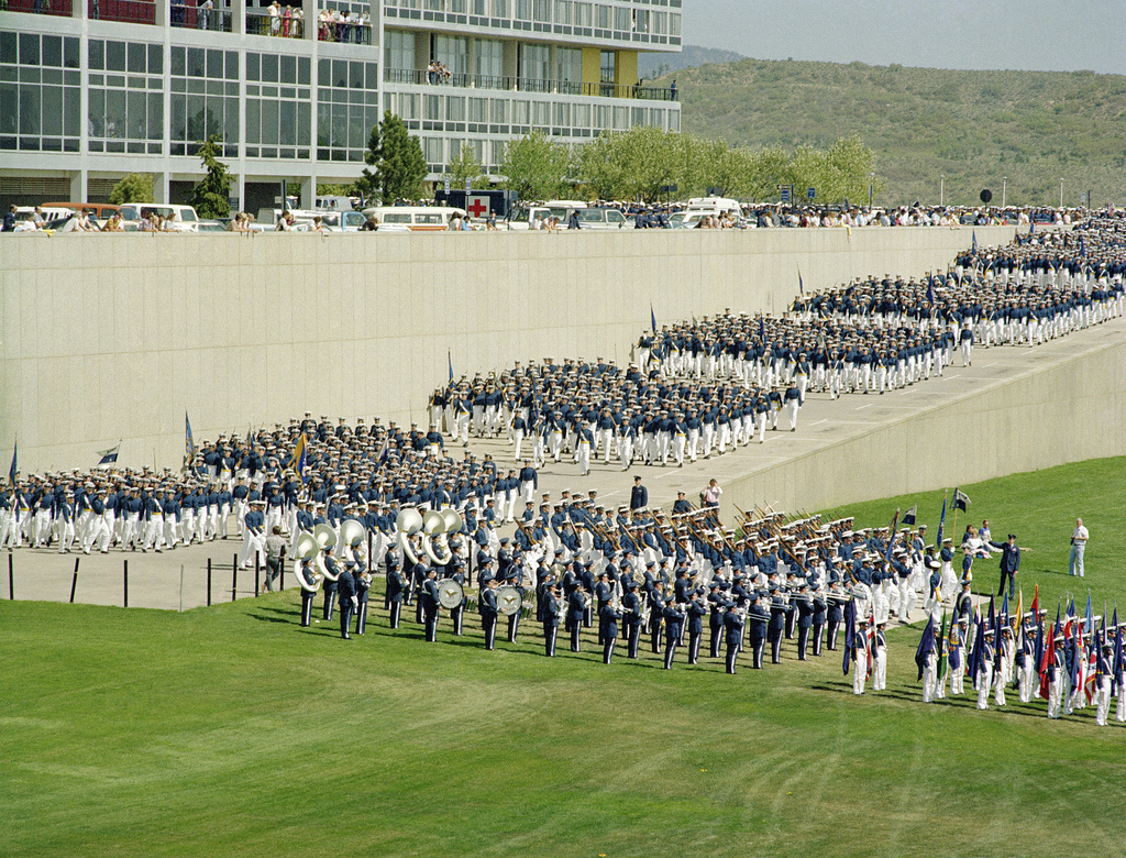 Led by a color guard and the US Air Force Academy Band, cadets prepare to march onto the academy parade ground