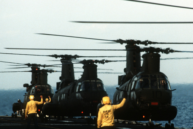 Plane directors signal instructions to three CH-46 Sea Knight helicopters preparing to depart the amphibious assault ship USS IWO JIMA (LPH-2) during the joint service Exercise Ocean Venture '84