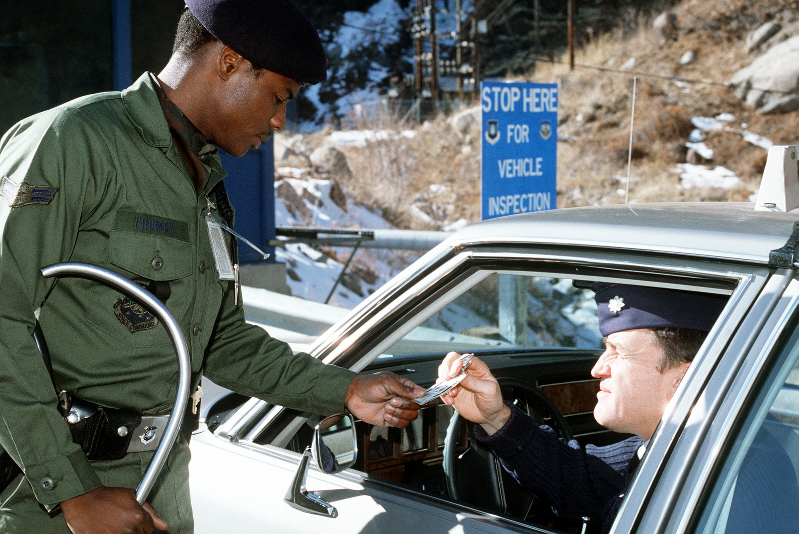 Security police law enforcement specialist checks the identification of an Air Force LTC arriving in his automobile at the NORAD Cheyenne Mountain Complex near Colorado Springs, Colorado. Exact Date Shot Unknown