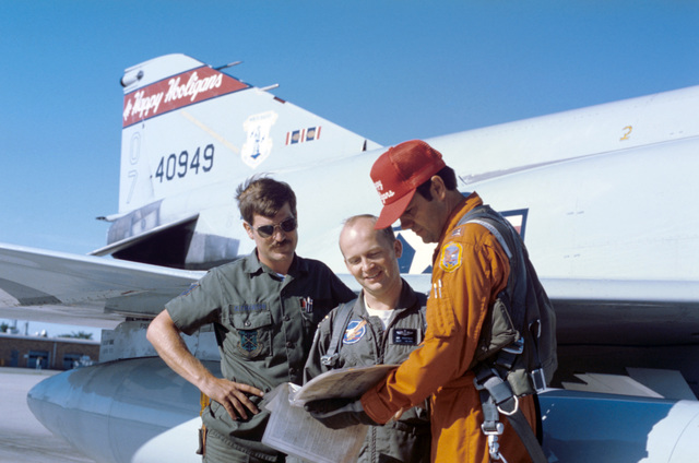 U.S. Air Force personnel assigned to the 119th Fighter Wing, North Dakota Air National Guard, examine their flight logbook in front of a F-4D Phantom II aircraft on the flight line at Hector International Field, in Fargo, N.D. Pictured left to right: TECH. SGT. James E. Clemenson; 2nd LT. James Thompson; and CAPT. Michael J. Haugen. (A3604) (U.S. Air Force PHOTO) (Released)