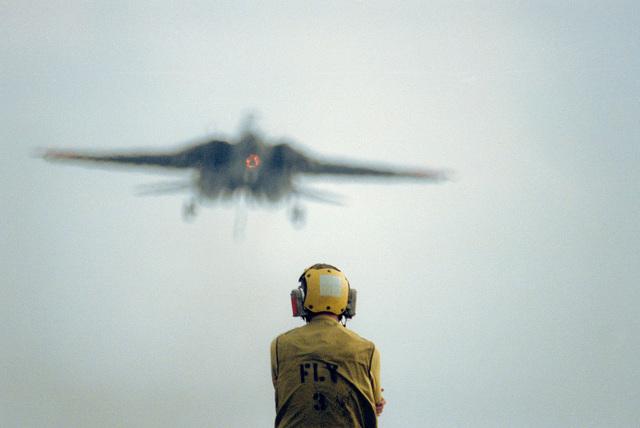 A crewman watches from the flight deck of the aircraft carrier USS AMERICA (CV-66) as an F-14 Tomcat aircraft approaches for a landing