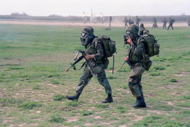 Marines of Company A, Battalion Landing Team 1/3, wearing Nuclear, Biological, Chemical (NBC) protective masks, move forward during a mock assault. They are participating in Operation KERNAL BLITZ