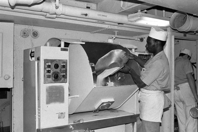 Mess Management SPECIALIST SEAMAN (MSSN) Irving Lyons pours sugar into the bread dough mixer aboard the aircraft carrier USS AMERICA (CV 66)