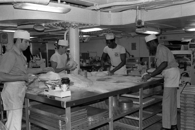 Mess Management Specialists form loaves of bread aboard the aircraft carrier USS AMERICA (CV 66)