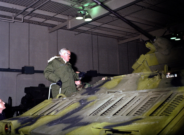Retired US Senator Barry M. Goldwater stands on a ladder to view an M2 Bradley infantry fighting vehicle during his tour of the US Army Armor Center