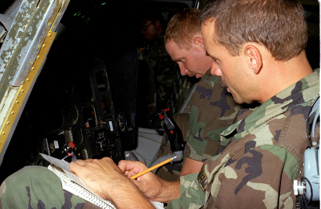 Private First Class Robert L. Douglas and Private 2 Frank Fairbanks study the navigation system of the OH-58 Coyote helicopter during training at Brandt Hall