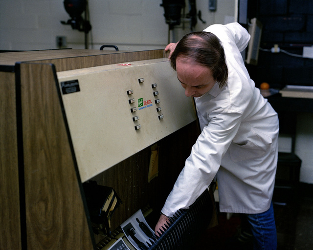 Civilian technician Andy Pike removes a finished print from a Kreonite 31-inch black-and-white processor
