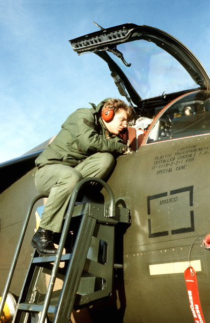 A technician works in the cockpit of an F-111D aircraft during maintenance operations on the flight line