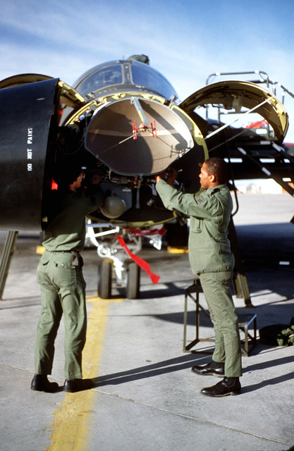 Integrated avionics attack control systems specialists from the 524th Tactical Fighter Training Squadron service the attack and guidance radar system of an F-111D aircraft