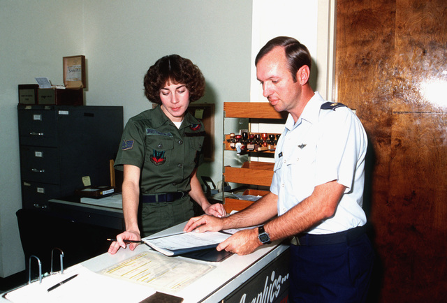 Major James Lumner, a Tactical Air Warfare Center (TAWC) project officer and course manager for the wing commanders course, discusses a work request with STAFF Sergeant Ann Butterfield, assistant non-commissioned officer in charge of the TAWC graphics section