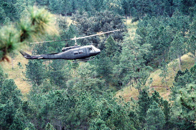 A UH-1 Iroquois helicopter, carrying General Gustavo Adolfo Alvarez Martinez, chief of the Honduran armed forces, flies over San Estaban Valley. The general is arriving in the area to observe a parachute drop by Honduran troops during Exercise AHUAS TARA (BIG PINE) II