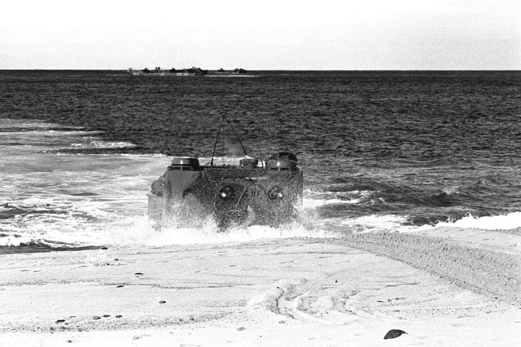 Marines come ashore on Makua Valley Beach in a tracked landing vehicle, personnel (LVTP 7) during Operation KERNEL BLITZ. The LVTP 7 is assigned to 3rd Amphibious Assault Battalion, 1ST Marine Brigade. In the background is an LCU 1610 class utility landing craft (LCU 1617)