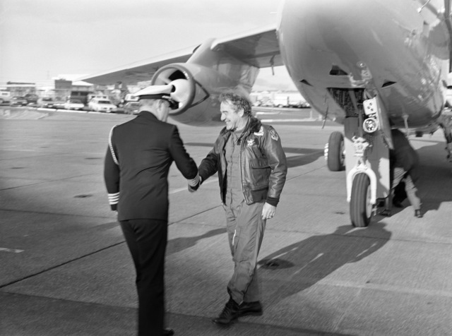 Captain J. A. McKenzie, CHIEF of STAFF, greets Melvin R. Paisley, Assistant Secretary of Defense for Research and Engineering, upon his arrival for a visit with Attack Squadron 128 (VA-128)