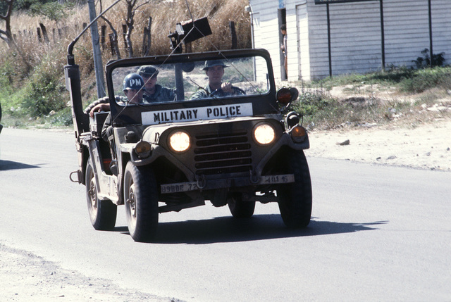A military police jeep leads a supply convoy into town while on the way to San Lorenzo during Exercise AHUAS TARA (BIG PINE) II. The convoy is being conducted by Company B, 46th Engineers, from Fort Rucker, Alabama