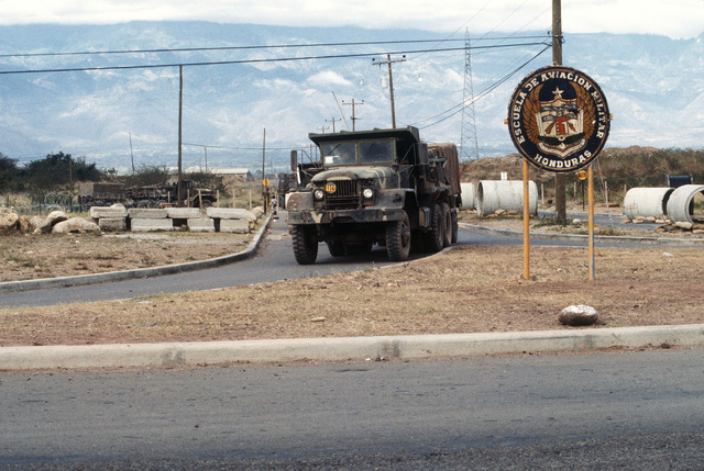 A supply convoy passes the main gate of Palmerola Air Base as it leaves for San Lorenzo during Exercise AHUAS TARA (BIG PINE) II. The convoy is being conducted by Company B, 46th Engineers, from Fort Rucker, Alabama