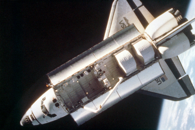 An overhead view of the space shuttle Challenger taken by a fixed camera mounted on astronaut Bruce McCandless's helmet during the first extravehicular activity (EVA) using the nitrogen-propelled, hand-controlled, manned maneuvering unit (MMU). The MMU is a device which allows astronauts to move freely in space without a tether