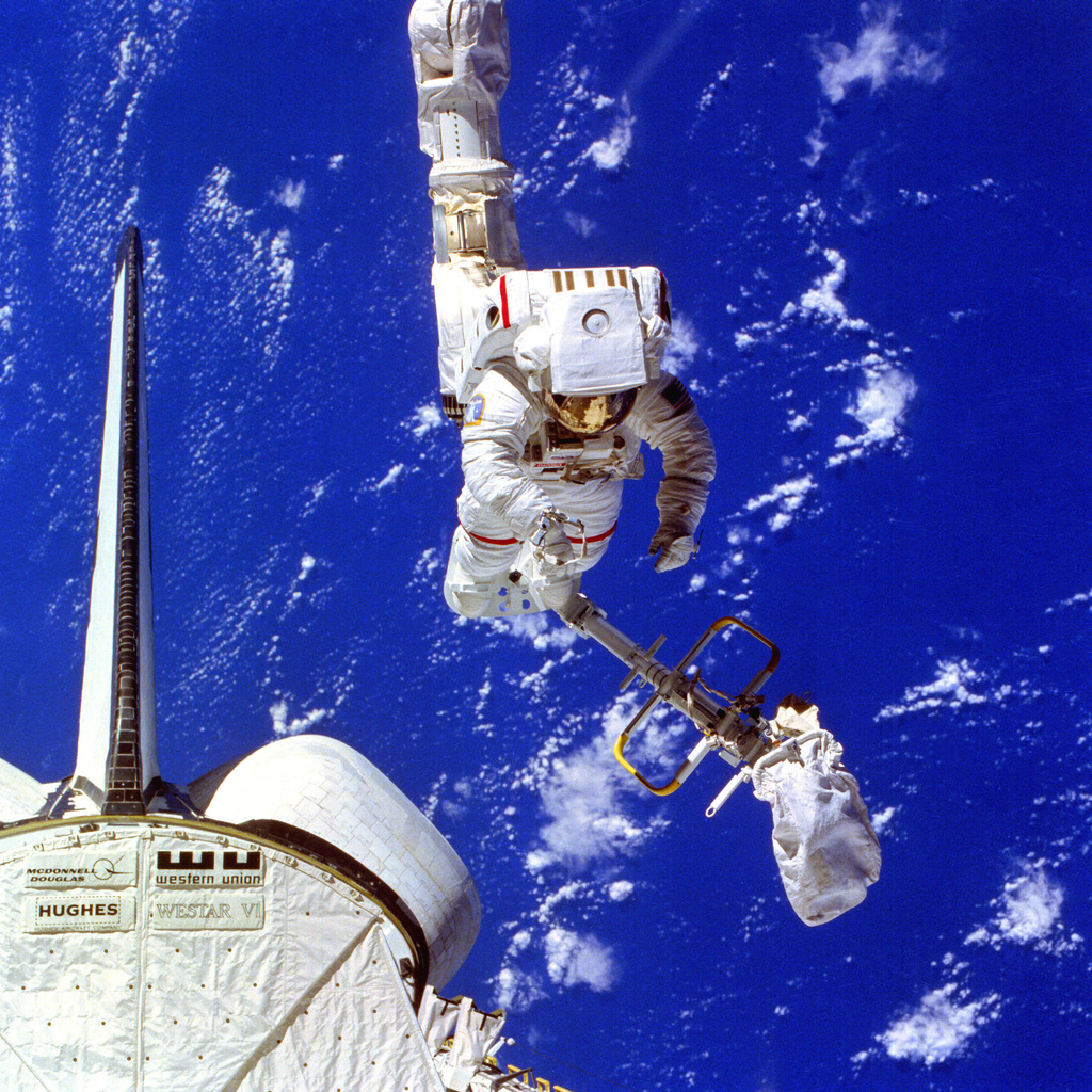 Astronaut Bruce McCandless II conducts an extravehicular activity (EVA) during Flight 41-B of the space shuttle Challenger. McCandless's boots are attached to a mobile foot restraint (MFR), which is attached to the end of the remote manipulator system (RMS) arm. The RMS is a cherry picker device used for maneuvering around outside the spacecraft