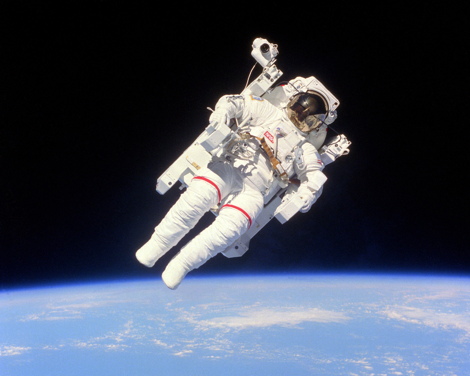 Astronaut Bruce McCandless II floats a few meters away from the cabin of the earth-orbiting Space Shuttle Challenger as part of an historic Extravehicular Activity (EVA) during Flight 41-B. This is the first use of the nitrogen-propelled, hand-controlled device called the Manned Maneuvering Unit (MMU), which allows astronauts to move freely in space without a tether