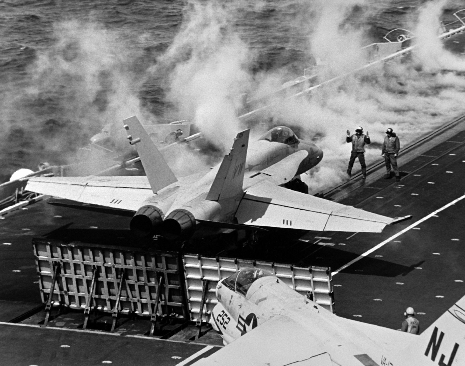 Right rear view of an F/A-18 Hornet aircraft assigned to Marine Fighter Attack Squadron 314 (VMFA-314) preparing for takeoff from the aircraft carrier USS CONSTELLATION (CV-64) during an operational evaluation (OPEVAL). In the foreground is an A-7 Corsair  II aircraft from Light Attack Squadron 122 (VA-122)