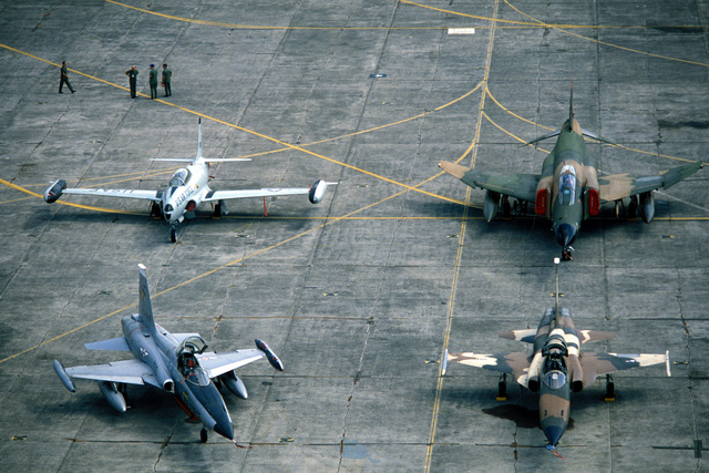 A view of a Philippines Air Force F-5E Tiger II aircraft, left front, a USAF T-33 Shooting Star aircraft, left rear, a USAF F-5E Tiger II aircraft, right front, and a USAF F-4 Phantom II aircraft parked on the flight line during Exercise COPE THUNDER '84