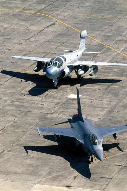 A view of an F-16 Fighting Falcon aircraft from the 8th Tactical Fighter Wing, front, and a Marine EA-6B Prowler aircraft, parked on the flight line during Exercise COPE THUNDER '84
