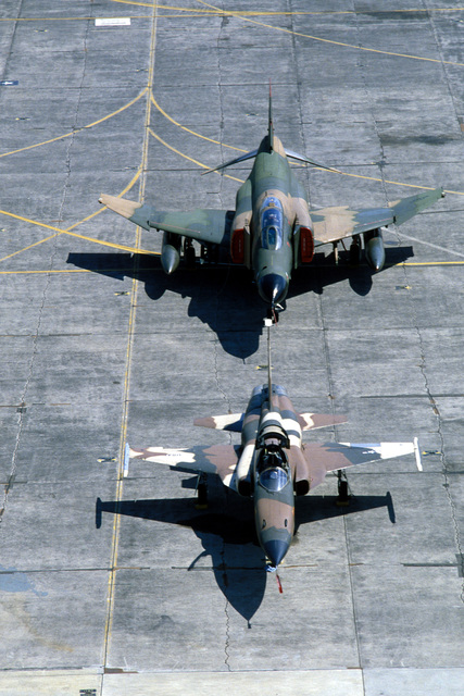 A view of an F-5E Tiger II aircraft, front, and an F-4 Phantom II aircraft from the 3rd Tactical Fighter Wing, parked on the flight line during Exercise COPE THUNDER '84