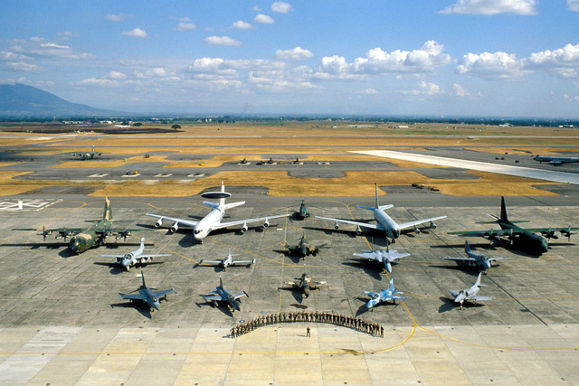 Participates of Exercise COPE THUNDER '84, including the Royal Thai and Philippines Air Forces, stand in front of a formation of various aircraft on the flight line at the conclusion of the exercise