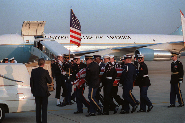 A joint service casket team carries the flag draped casket of Leamon R. Hunt from a VC-135 aircraft upon its arrival. Mr. Hunt was the director of the Multi-National Force and Observers headquarters in Rome, Italy