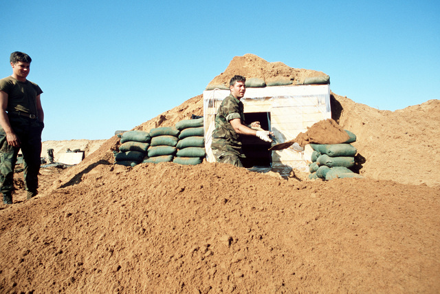 A Marine of the 22nd Marine Amphibious Unit fortifies a bunker as another Marine looks on, just prior to redeployment from the city at the conclusion of their participation in a multinational peacekeeping operation
