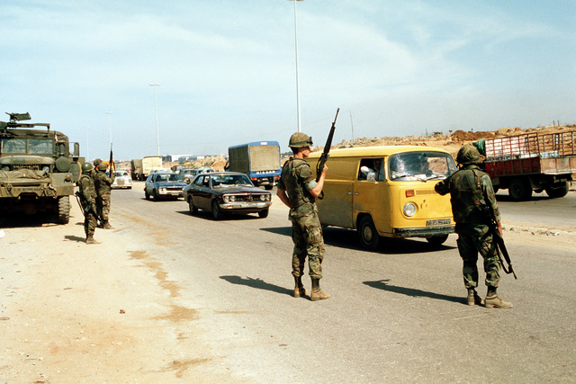 Marines from the 22nd Marine Amphibious Unit provide security on a beach road during redeployment from the city, at the conclusion of their participation in a multinational peacekeeping operation