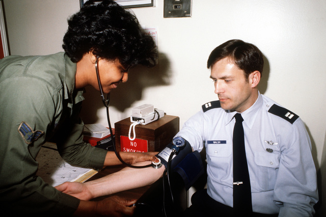 Sergeant Melba Tyson gives Captain Donald Walsh a blood pressure test during his physical examination at the base hospital