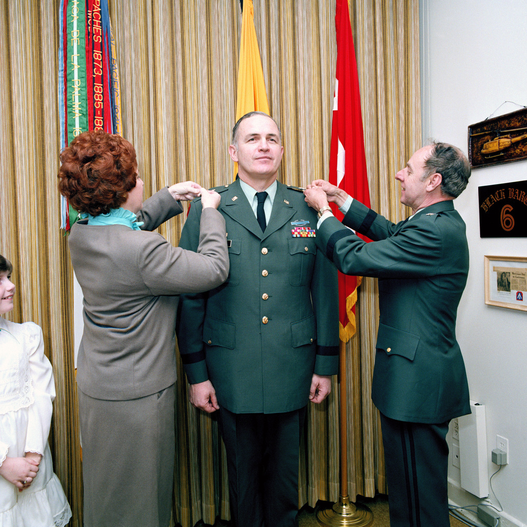 Lieutenant General (LGEN) James H. Merryman, deputy chief of staff of research, development and acquisition, pins a second star on the shoulder of Major General (MGEN) Donald S. Pihl during a frocking ceremony at the Pentagon.  Assisting is Pihl's wife Sandy