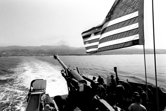 A utility landing craft carrying members of Hotel Battery, 22nd Marine Amphibious Unit, and an M198 155 mm howitzer, moves toward the tank landing ship USS BARNSTABLE COUNTY (LST 1197) (not visible) during the unit's redeployment at the conclusion of a multinational peacekeeping operation