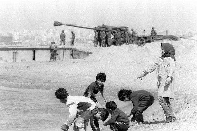 Lebanese children play in the surf at Green Beach during the redeployment of the 22nd Marine Amphibious Unit back to ships of Amphibious Squadron 4, at the conclusion of a multinational peacekeeping operation. In the background an M198 155 mm howitzer is prepared for loading onto a utility landing craft