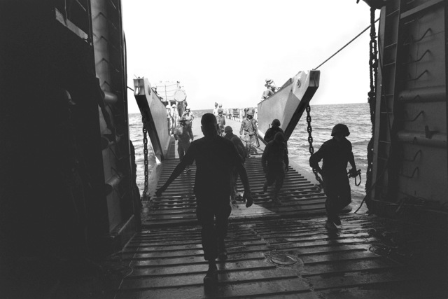 Marines of the 22nd Marine Amphibious Unit come aboard the tank landing ship USS BARNSTABLE COUNTY (LST 1197) from a utility landing craft, during their redeployment from Beirut at the conclusion of a multinational peacekeeping operation