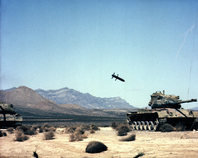 A Copperhead laser-guided anti-tank missile fired from a towed M198 155 mm Howitzer approaches a target tank