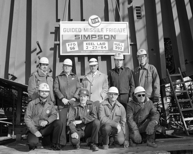 Shipyard workers and Navy officers pose during the keel laying of the guided missile frigate USS SIMPSON (FFG 56)