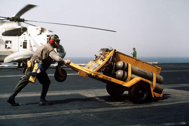 A flight deck crewman aboard the nuclear-powered aircraft carrier USS ENTERPRISE (CVN 65) pushes an NAN-2 nitrogen servicing unit across the flight deck. The ship is participating off the coast of Lebanon