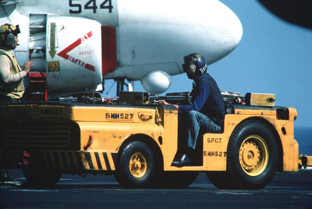 A flight deck crewman operates an MD-3 tow tractor on the flight deck of the aircraft carrier USS JOHN F. KENNEDY (CV 67) during operations off the coast of Lebanon. The nose section of an A-6E Intruder aircraft is visible in the background